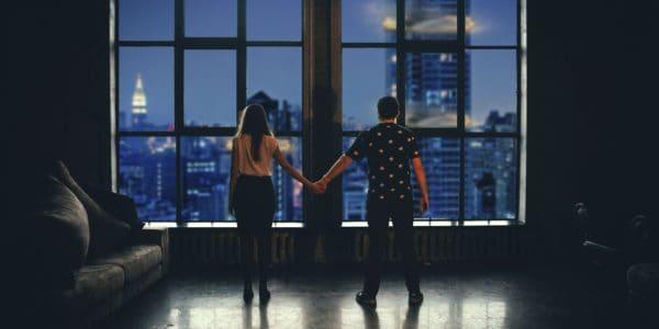 Ein Mann und eine Frau auf Abstand Händchen haltend in einem Penthouse vor Hochhauskullisse